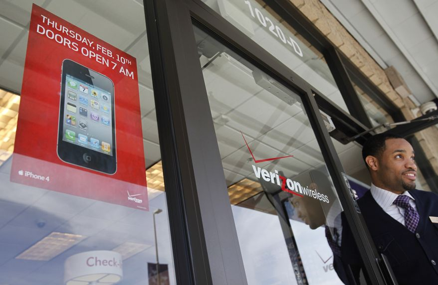 **FILE** Verizon Wireless store salesman Antione Haynes looks out the front door of a Verizon store with an Apple iPhone advertisement in foreground in Mountain View, Calif., on Feb. 3, 2011. (Associated Press)