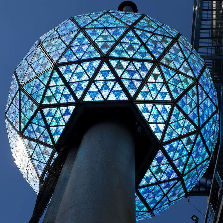 The Times Square New Year's Eve Ball rises to the top of it's 135-foot spire, Friday, Dec. 30, 2011, in New York. A crowd cheered as the ball dropped in a dress rehearsal around noon Friday as preparations continued for New York's big welcome party for 2012. (AP Photo/John Minchillo)