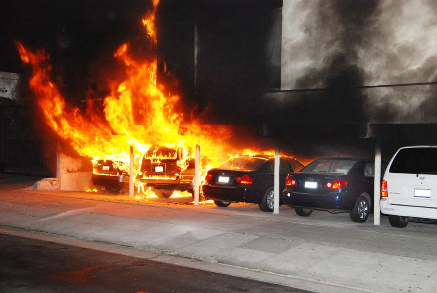 Burning cars are shown at the site of an arson fire in the Hollywood section of Los Angeles on Friday Dec.30, 2011. An arsonist torched car after car early Friday, sending firefighters scrambling to put out more than a dozen blazes in Hollywood and neighboring West Hollywood. (AP Photo/Mike Meadows)