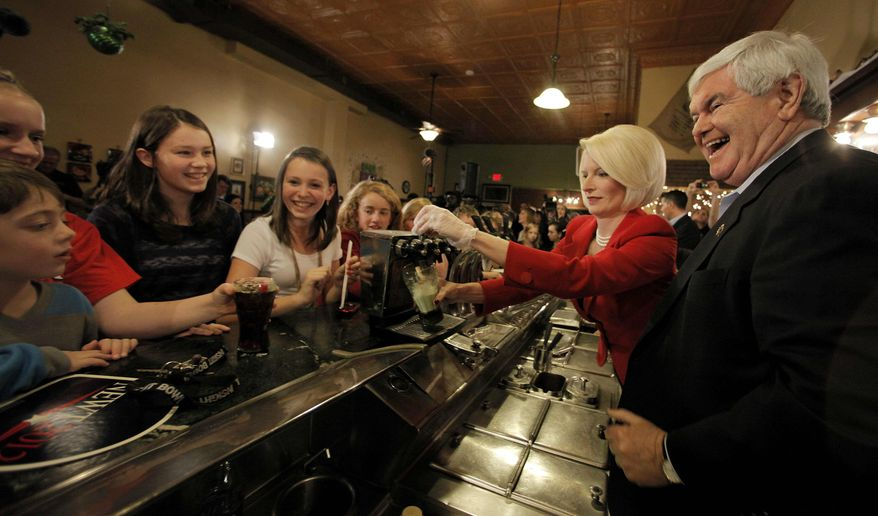 Republican presidential candidate, former House speaker Newt Gingrich, right, and his wife Callista serve drinks to children during at campaign stop a Adams Street Espresso in Creston, Iowa, Friday, Dec. 30, 2011. (AP Photo/Charlie Riedel)