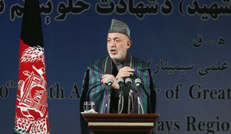 Afghan President Hamid Karzai adjusts his coat, as he speaks during a gathering to mark the 40th death anniversary of political leader Khan Abdul Samad Khan Achekzai in Kabul, Afghanistan, Saturday, Dec. 31, 2011. Karzai welcomed on Saturday remarks from the Obama administration saying that Taliban insurgents were not America's enemies. (AP Photo/Musadeq Sadeq)