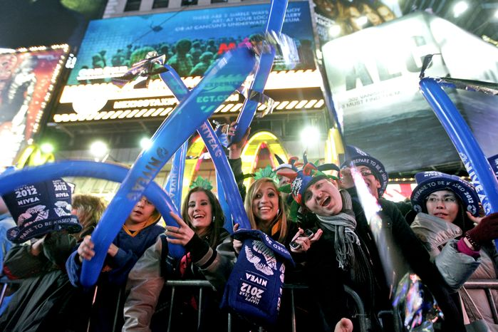 Samantha Rhodes, center, and Samantha Mitchell, of North Port, Fl., cheer during the New Year's Eve celebration in New York's Times Square, Saturday, Dec. 31, 2011 (AP Photo/Mary Altaffer)