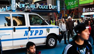 ** FILE ** Pedestrians pass police vans in Times Square as city police officials begin ramping up security before Saturday's New Year's Eve celebrations, on Friday, Dec. 30, 2011, in New York. Behind the scenes, the police meticulously map out how to control crowds that can swell to 1 million while also preparing for potential terror threats. (AP Photo/John Minchillo)