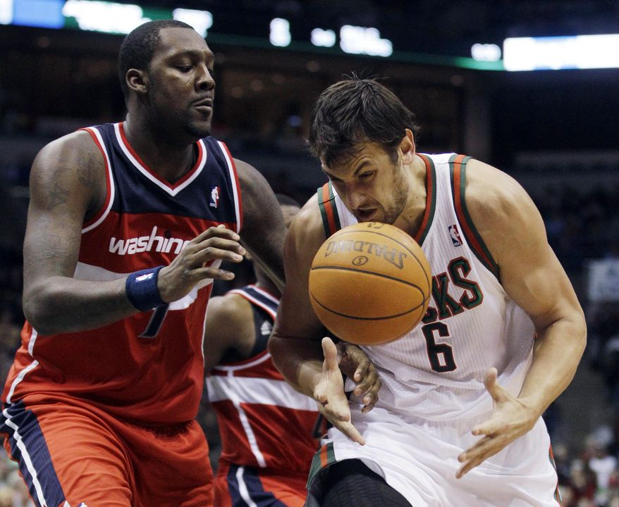 Milwaukee Bucks' Andrew Bogut loses the ball as he tries to drive past Washington Wizards' Andray Blatche (7) during the second half of an NBA basketball game Friday, Dec. 30, 2011, in Milwaukee. (AP Photo/Morry Gash)