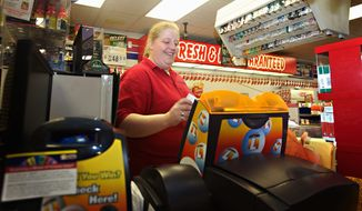 "Amber Wallenstein, a clerk at the Freedom Value Center convenience store and gas station in Sioux Falls, S.D., rings up a Powerball ticket for a customer. The price for the multistate Powerball tickets is set to double Jan. 15. ""I don't think anybody knows about it yet,"" Ms. Wallenstein said of the price hike. ""But they'll still pay for it."" (Associated Press)"