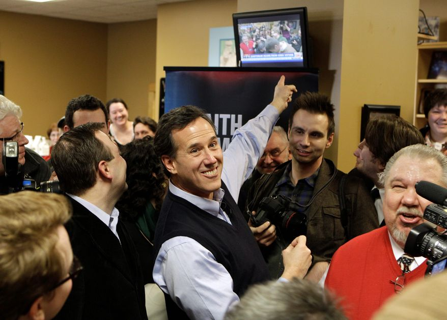 Republican presidential hopeful Rick Santorum points to a television showing his campaign stop Sunday at the Daily Grind coffee shop in Sioux City, Iowa. Mr. Santorum is enjoying a surge ahead of Tuesday's Iowa caucuses. (Associated Press)