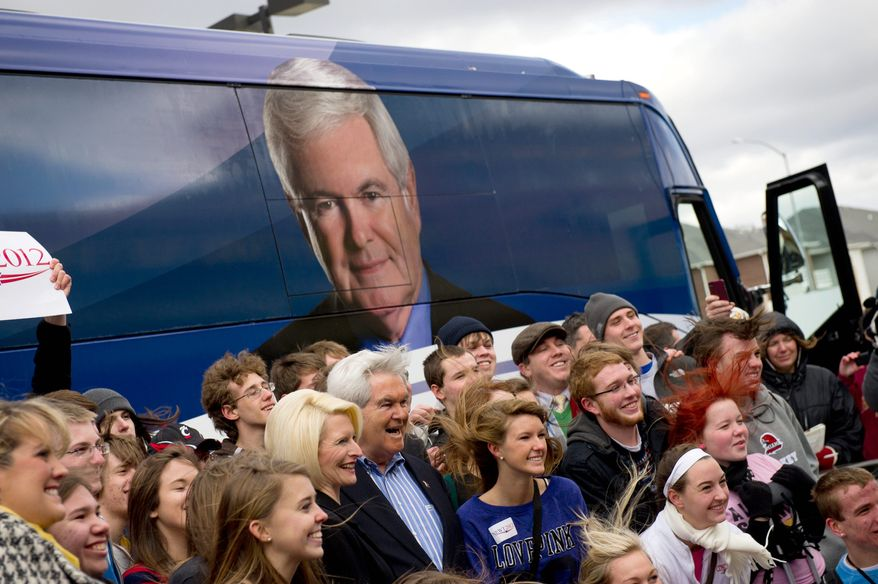 Juniors and seniors from Taylor High School in Cincinnati pose for a photo amid strong, cold winds with Republican presidential hopeful Newt Gingrich and wife Callista outside of the West Towne Pub in Ames, Iowa, where he was meeting Sunday with supporters. (Andrew Harnik/The Washington Times)