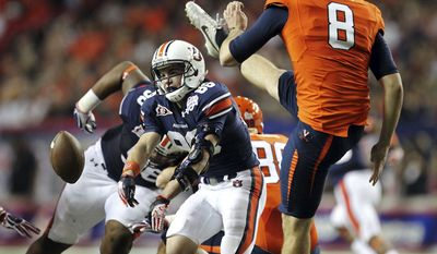 Auburn's Garrett Harper (86) blocks a punt by Virginia's Jimmy Howell (8) in the first quarter of the Chick-fil-A Bowl on Saturday, Dec. 31, 2011, in Atlanta. (AP Photo/Atlanta Journal & Constitution, Jason Getz)