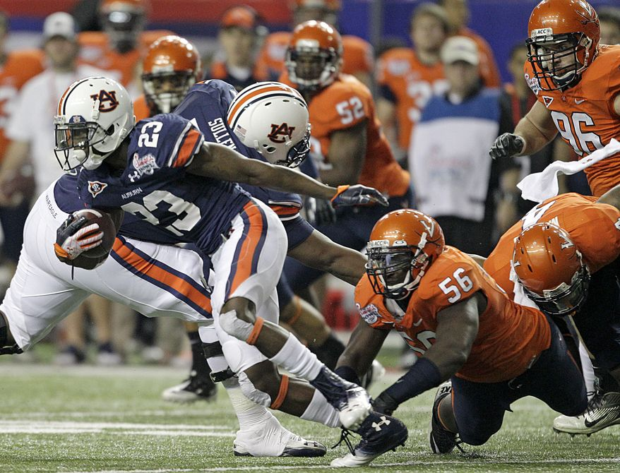 Auburn running back Onterio McCalebb (23) escapes the reach of Virginia defensive end Cam Johnson (56) during he Chick-fil-A Bowl game Saturday, Dec. 31, 2011, in Atlanta. (AP Photo/David Goldman)