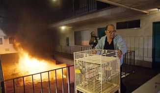 Los Angeles Fire Department firefighters assist a man out of his apartment along with a cage of birds as multiple cars burn in a carport in the Sun Valley neighborhood of Los Angeles on Saturday, Dec. 31, 2011. (AP Photo/Dan Steinberg)