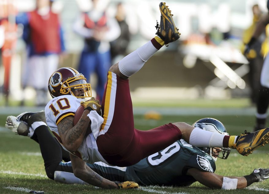 Jabar Gaffney (10) of the Washington Redskins lands after a tackle by the Philadelphia Eagles' Nate Allen (29) during the first half of an NFL game on Sunday, Jan. 1, 2012, in Philadelphia. (AP Photo/Michael Perez)