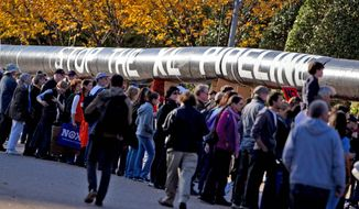 **FILE** Demonstrators outside the White House march in November with a replica of a pipeline during a protest of the planned Keystone XL pipeline that would bring tar sands oil from Canada to Texas. (Associated Press)