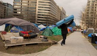 Forest Bailey, of the District, walks past a platform where a former Occupy D.C. encampment protester's tent has been removed as he carries an air mattress to another demonstrator in McPherson Square in Northwest on Monday Jan. 2. (Barbara L. Salisbury/The Washington Times)