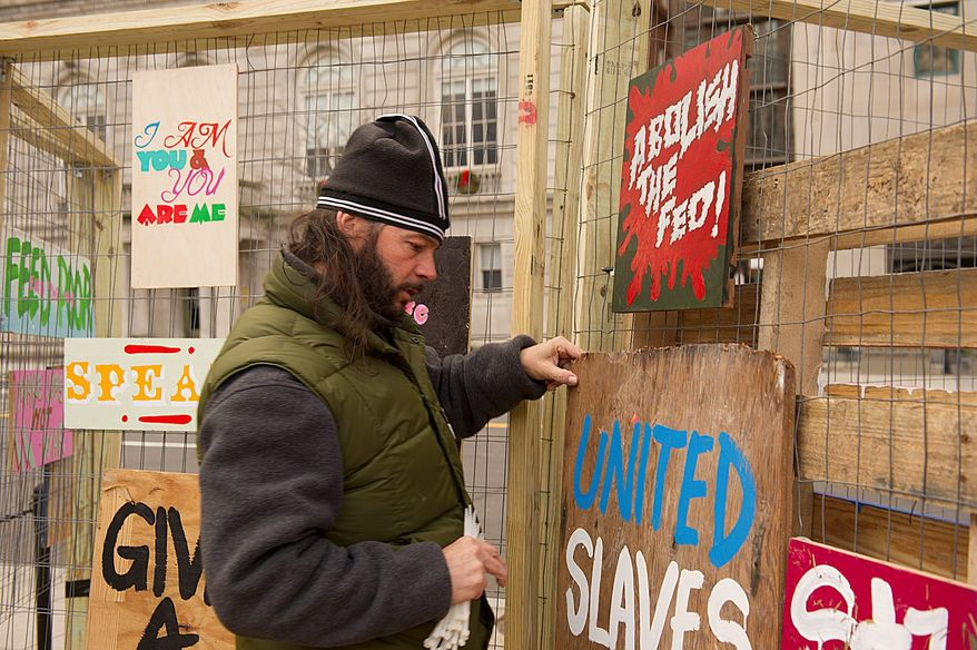 Occupy D.C. activist John Zangas, of the District, Monday replaces artwork torn down by police at the McPherson Square encampment in Northwest. Mr. Zangas says he has been part of the encampment since it began in October and has talked to many people he wouldn't have met otherwise. (Barbara L. Salisbury/The Washington Times)