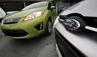 **FILE** A Lime Squeeze Metallic 2012 Ford Fiesta SE (left) and an Ingot Silver Metallic 2012 Ford Focus Titanium 5-door hatchback are seen Aug. 31, 2011, at the Maroone Ford of Miami dealership in Miami. (Associated Press)