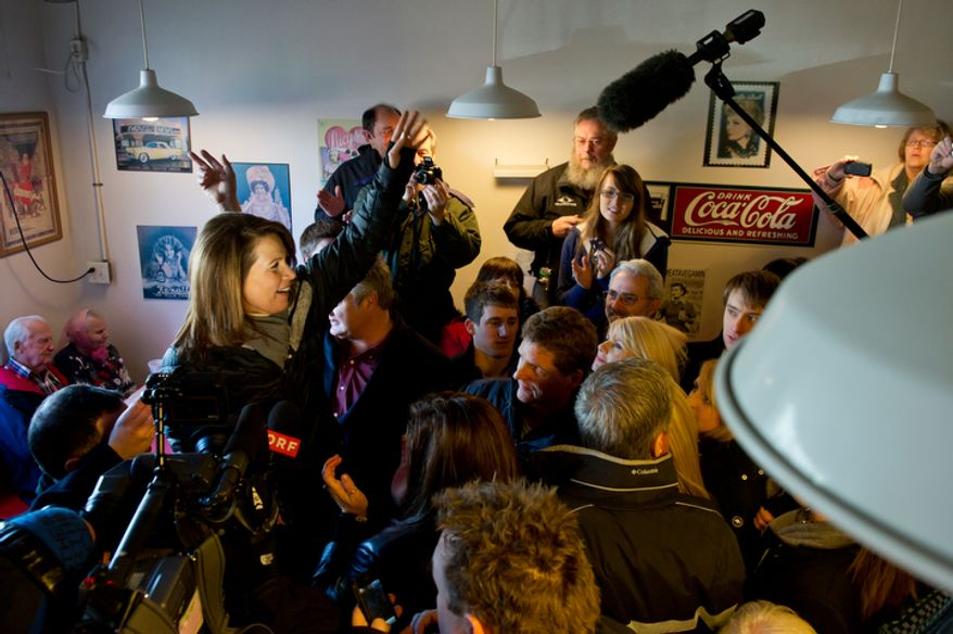 Republican presidential candidate Michele Bachmann waves to a packed room as she visits Paula's Maid Rite Restaurant. (Andrew Harnik / The Washington Times)
