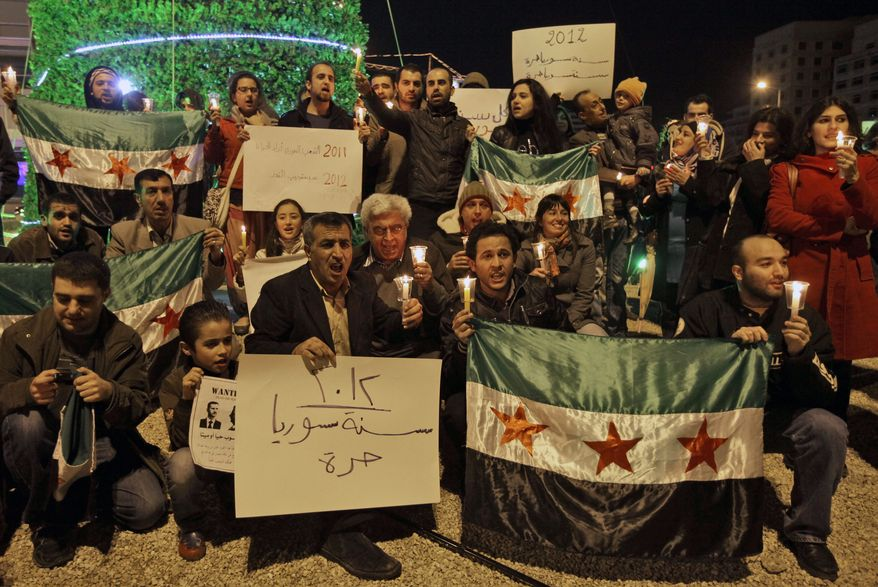 "Lebanese and Syrian activists hold Syrian revolutionary flags on Saturday, Dec. 31, 2011, during a candlelight vigil in downtown Beirut in mourning Syrians killed since the uprising against President Bashar Assad's regime began in March. The banner in Arabic reads, ""2012 Syria is free."" (Associated Press)"