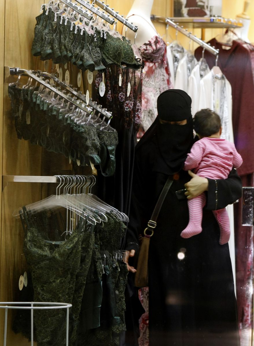 **FILE** A Saudi woman holding a child checks out lingerie March 25, 2009, at a store in Riyadh, Saudi Arabia. (Associated Press)
