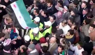 In this image from amateur video, Arab League observers are seen Dec. 30, 2011, at a protest in Idlib, Syria. Hundreds of thousands of Syrians poured into the streets across the nation in the largest protests in months, shouting for the downfall of the regime in a defiant display invigorated by the presence of Arab observers, activists said. (Associated Press/Shaam News Network via APTN)