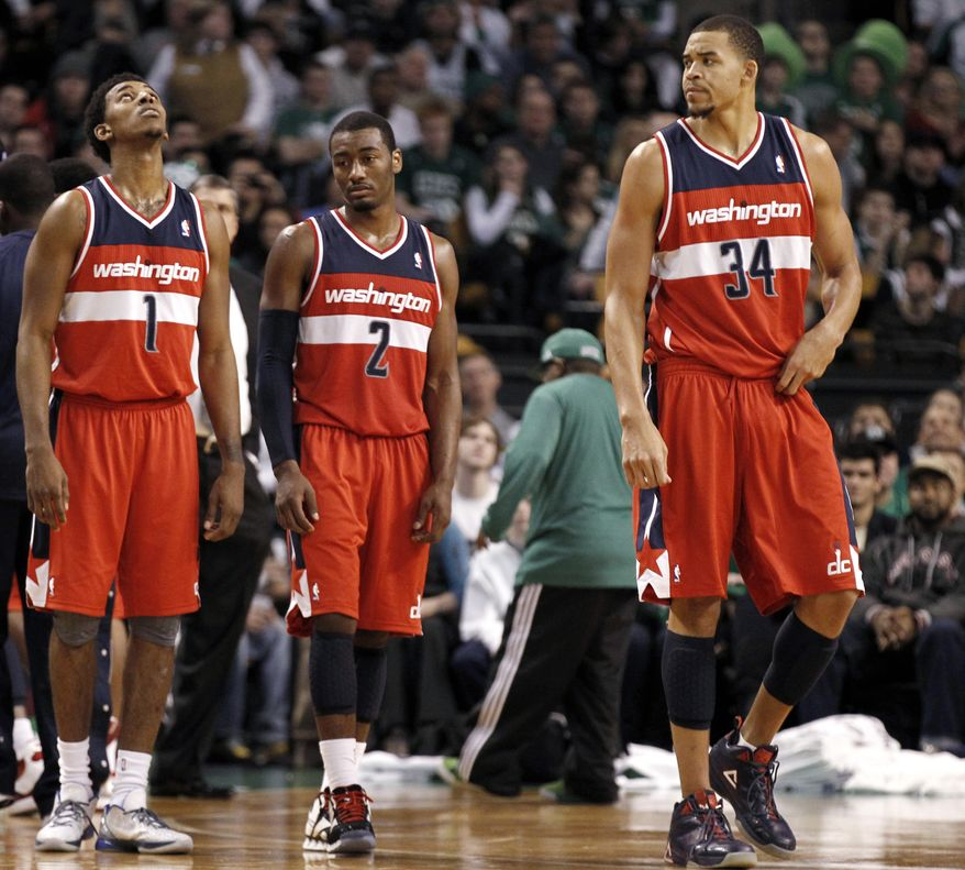Washington Wizards' Nick Young (1), John Wall (2) and JaVale McGee wait for play to resume during the fourth quarter of the Wizards' 100-92 loss to the Boston Celtics in an NBA game in Boston Monday, Jan. 2, 2012. (AP Photo/Winslow Townson)