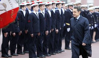 """French President Nicolas Sarkozy reviews sailors in Lanveoc-Poulmic before a speech in which he called the violence in Syria """"a massacre."""" (Associated Press)"""