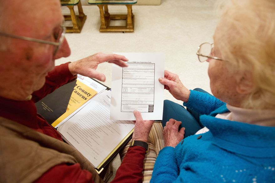Art Joens helps Rosalia Brandt sign in during an Iowa caucus meeting Tuesday at his home in Manilla. The Joenses host one of the few remaining caucus meetings at a private residence in the state. (Andrew Harnik/The Washington Times)