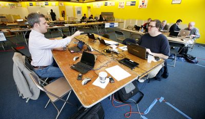 ** FILE ** Volunteers Jason Bassett, of Des Moines, Iowa, left, and Mark Hancock, of Windsor Locks, Conn., right, work at Republican presidential candidate, former Massachusetts Gov. Mitt Romney's campaign headquarters, Friday, Dec. 30, 2011, in Des Moines, Iowa. (AP Photo/Charlie Neibergall)