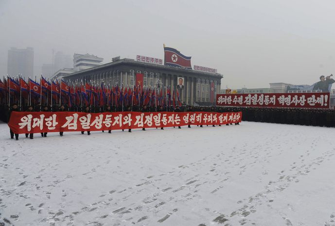 "Thousands of North Koreans gather in Pyongyang, North Korea, at Kim Il Sung Square to hold a mass rally in support for their country's policies and new leader Kim Jong Un on Jan. 3, 2012. The banner carried reads, ""Let's uphold thoroughly Great Leader Comrade Kim Jong Il's legacy."" (Associated Press)"