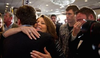 A member of Rep. Michele Bachmann's team wipes tears from his eyes as the former Republican presidential hopeful hugs family and staff members after announcing in West Des Moines, Iowa, on Wednesday that she would end her campaign. She finished sixth in Tuesday's Iowa Republican caucuses. (Andrew Harnik/The Washington Times)