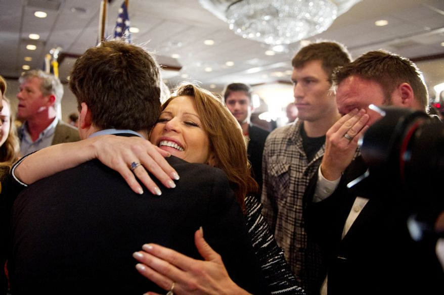 A member (right) of Rep. Michele Bachmann's campaign team wipes away tears as Mrs. Bachmann hugs family and staff members after announcing in West Des Moines, Iowa, on Wednesday, Jan. 4, 2012, that she will end her Republican presidential campaign. (Andrew Harnik/The Washington Times)