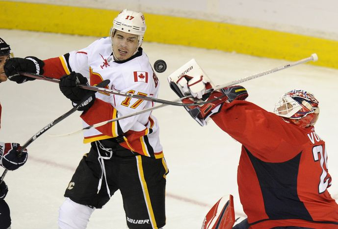 Washington Capitals goalie Tomas Vokoun reaches out for the puck against Calgary Flames left wing Rene Bourque during the third period, Tuesday, Jan. 3, 2012, in Washington. The Capitals won 3-1, and Bourque was suspended for his elbow to the head of center Nicklas Backstrom. (AP Photo/Nick Wass)