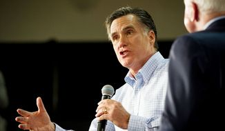 Former Massachusetts Gov. Mitt Romney (left) fields questions from the crowd during a presidential campaign stop at Manchester Central High School in Manchester, N.H., on Wednesday, Jan. 4, 2012. Sen. John McCain (right) endorsed Mr. Romney's bid for the GOP presidential nomination during the town-hall meeting. (Rod Lamkey Jr./The Washington Times)
