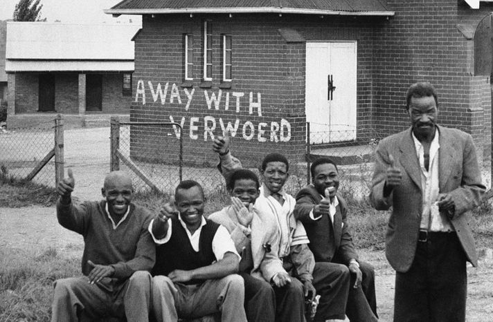"In 1960, members of the African National Congress take part in a day of mourning at Orlando East, near Johannesburg. Against all odds, the party of Nelson Mandela is celebrating its 100th anniversary in Bloemfontein on Sunday. The building in the background says, ""Away with Verwoerd."" H.F. Verwoerd was South Africa's prime minister and a strong proponent of the racial policies that led to a mass shooting at Sharpesville. (Associated Press)"