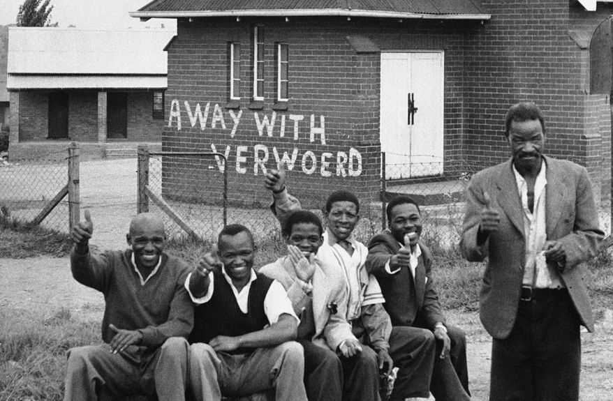 """In 1960, members of the African National Congress take part in a day of mourning at Orlando East, near Johannesburg. Against all odds, the party of Nelson Mandela is celebrating its 100th anniversary in Bloemfontein on Sunday. The building in the background says, """"Away with Verwoerd."""" H.F. Verwoerd was South Africa's prime minister and a strong proponent of the racial policies that led to a mass shooting at Sharpesville. (Associated Press)"""