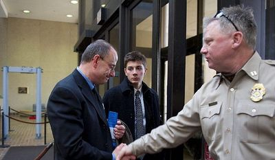 Patrick Hoover (left) shakes hands with a Montgomery County sheriff's officer on his way out of Maryland Circuit Court in Rockville on Thursday after the sentencing hearing for the driver in a May 15 crash that killed Mr. Hoover's son John, 20, and two other young people. (Barbara L. Salisbury/The Washington Times)