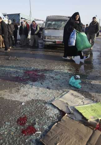 People gather at the scene of a bomb attack in Sadr City, east of Baghdad, on Jan. 5, 2012. (Associated Press)