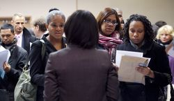 Job-seekers talk with a recruiter (center) at a job fair sponsored by National Career Fairs in New York on Monday, Dec. 12, 2011. (AP Photo/Mark Lennihan)