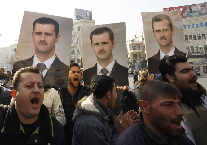 Pro-Syrian regime protesters shout slogans and hold portraits of Syrian President Bashar Assad during a demonstration Jan. 4, 2012, in Damascus, Syria, to show solidarity for Assad. (Associated Press)
