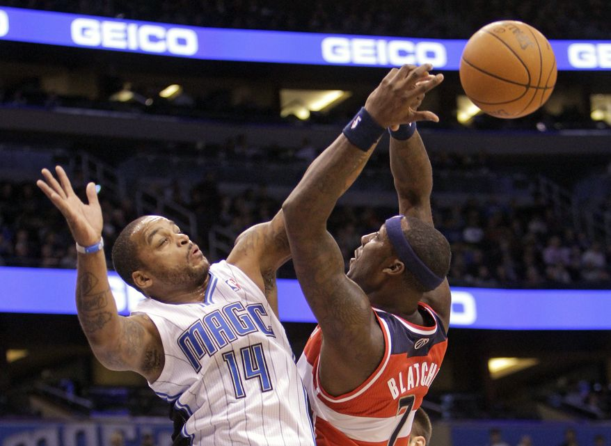 Orlando Magic guard Jameer Nelson (14) fouls Washington Wizards forward Andray Blatche as he tries to block a shot during the first half of Orlando's 103-85 victory on Jan. 4, 2012, in Orlando, Fla. (Associated Press)