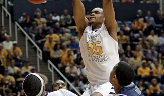 West Virginia's Keaton Miles dunks  over Georgetown's Otto Porter, right, during the second half in Morgantown, W.Va., on Saturday, Jan. 7, 2012. West Virginia won 74-62. (AP Photo/David Smith)