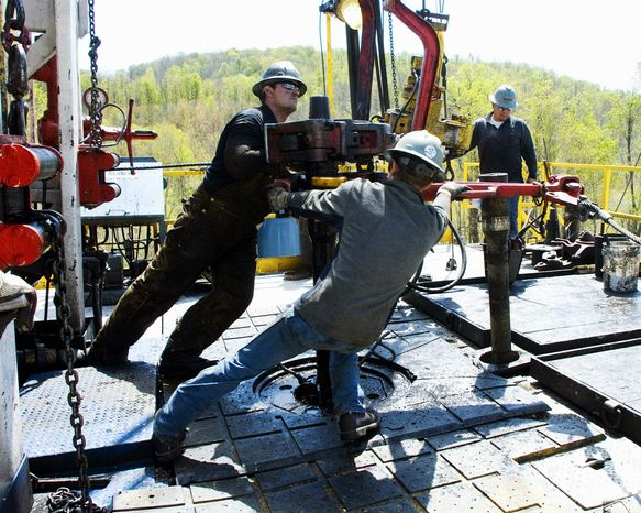 Workers move a section of well casing into place at a Chesapeake Energy natural gas well site near Burlington, Pa. Fracking uses water mixed with sand and chemicals to break underground rock and release large amounts of gas. (Associated Press)