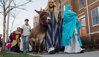 Manuel Sanchez and Rosmery Solorzano, playing Joseph and Mary, lead a Three Kings Day procession Sunday around the GALA Hispanic Theatre in Northwest. (Barbara L. Salisbury/The Washington Times)