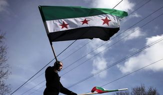 A Syrian immigrant waves Bulgarian and the revolutionary Syrian flag, during a rally against the regime of Syrian President Bashar al-Assad in front of the Syrian embassy in Sofia, on Sunday, Jan. 8, 2012. Syrian opposition groups say the death toll has risen beyond 6,000 and government forces continue to kill protesters despite the presence of Arab League monitors. (AP Photo/Valentina Petrova)