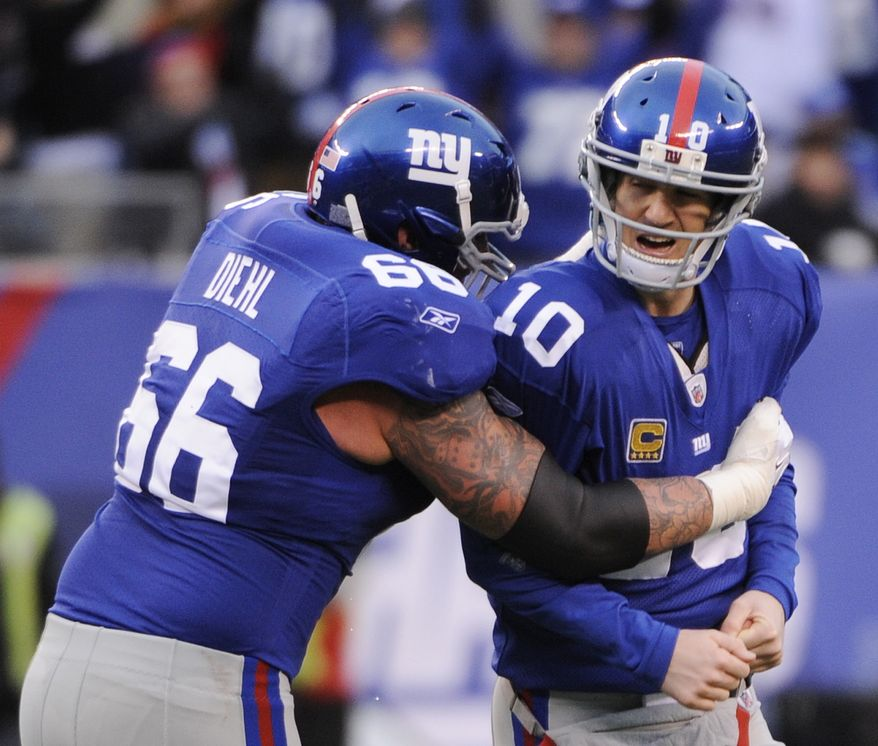 New York Giants guard David Diehl (66) hugs Eli Manning after his 27-yard touchdown pass to Mario Manningham during the second half of an wild card playoff game against the Atlanta Falcons Sunday, Jan. 8, 2012, in East Rutherford, N.J. (AP Photo/Bill Kostroun)