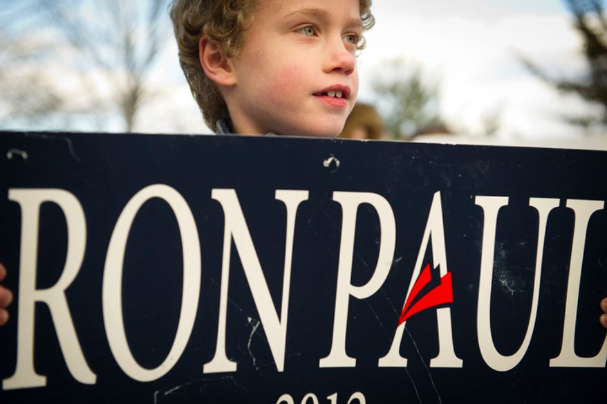 Michael James Lahey, 8, holds his sign as he and others wait for the arrival of Republican presidential candidate Ron Paul at Church Landing at Mill Falls in Meredith, N.H. (Rod Lamkey Jr/ The Washington Times)