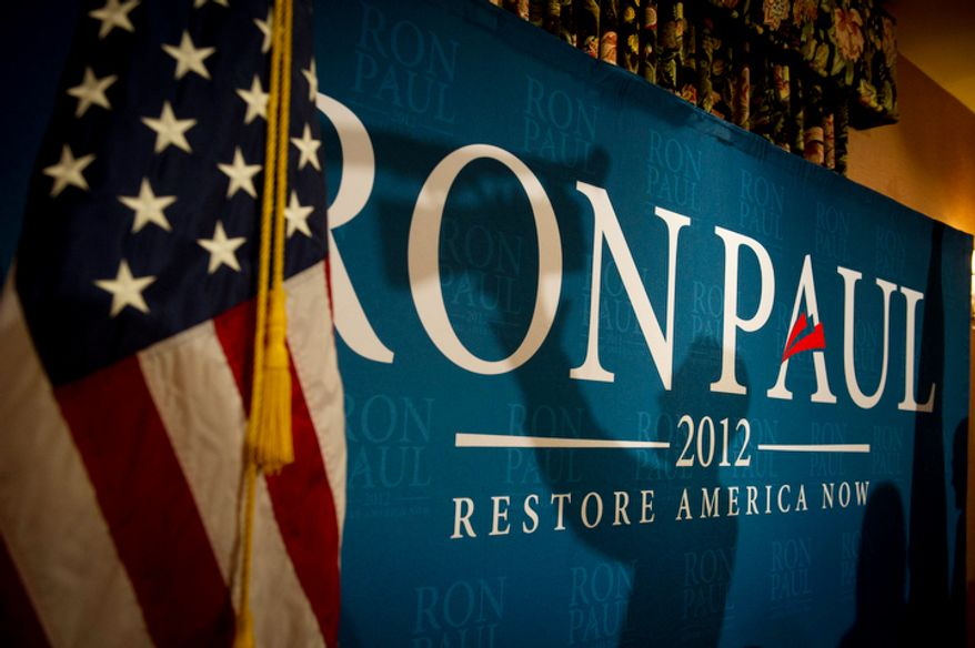 The shadow of a man with a video camera is seen on a banner where Republican presidential candidate Ron Paul is scheduled to speak during a town hall meeting at Church Landing at Mill Falls in Meredith, N.H. (Rod Lamkey Jr/ The Washington Times)