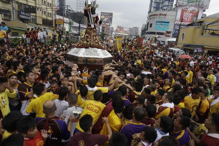 A replica of a centuries-old statue of Jesus Christ known as the Black Nazarene is carried by devotees during the blessing and procession of the replicas in Manila on Saturday, Jan. 7, 2012. (AP Photo/Aaron Favila)
