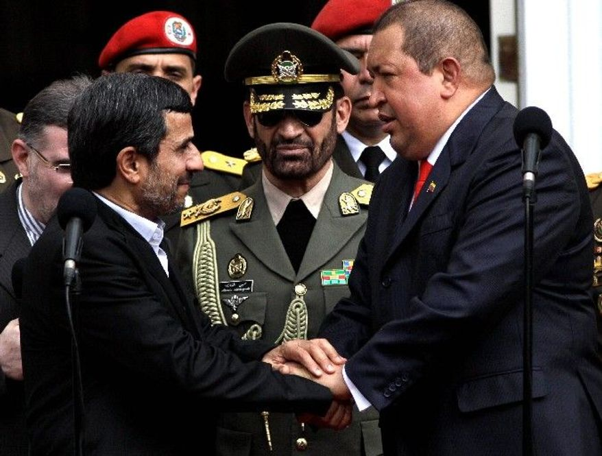 LIKE-MINDED: Iranian President Mahmoud Ahmadinejad (left) is welcomed Monday by Venezuelan President Hugo Chavez upon his arrival at the presidential palace in Caracas, Venezuela. The Iranian is visiting Latin America as tensions rise with the U.S. over a death sentence against an American man accused of being inside Iran on a special U.S. intelligence mission for the CIA. (Associated Press)