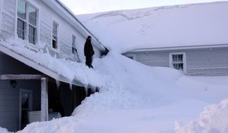 A man stands on the porch roof of a house buried in snow in the fishing town of Cordova, Alaska, on Saturday, Jan. 7, 2012. (AP Photo/Alaska Division of Homeland Security and Emergency Management, Kim Weibl)