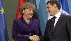 German Chancellor Angela Merkel and French President Nicolas Sarkozy shake hands after a news conference at the Chancellery in Berlin on Monday, Jan. 9, 2012. (AP Photo/Gero Breloer)